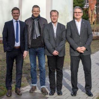 vier Männer vor Gebäude